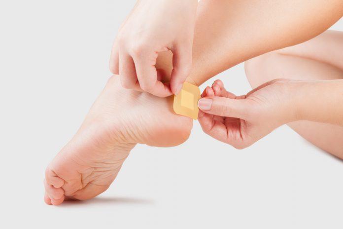 Imagem mostra uma pessoa colocando uma fita protetora no calcanhar do pé esquerdo para evitar ferimento ou bolha